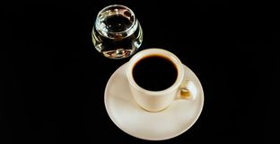 Svart kaffe i den vita koppen och ett exponeringsglas av sambuca med kaffe Royaltyfri Fotografi
