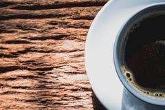 Svart kaffe i den vita koppen på den gamla wood bakgrunden Royaltyfria Bilder