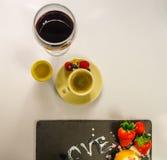 Svart kaffe i en kopp av kräm med jordgubben som är rasbberry Royaltyfria Foton