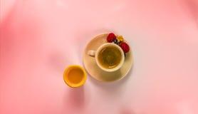 Svart kaffe i en kopp av kräm med rasberry och orange fruktsaft Arkivbild