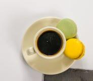 Svart kaffe i en kopp med två macarons med anstrykningar av citronen Royaltyfri Bild
