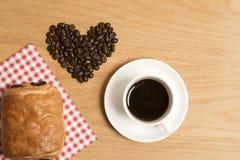 Svart kaffe i en kopp och ett tefat med en giffel och kaffebönor Arkivbilder