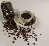 Svart kaffe i en vit kopp på ett tefat med en upturned krus Arkivfoto