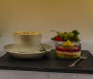 Svart kaffe i en vit kopp på ett tefat med piskad kräm och s Royaltyfria Bilder