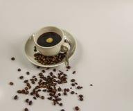 Svart kaffe i en vit kopp på tefatet med skeden och spillda kaffebönor Royaltyfri Fotografi