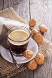 Svart kaffe i ett exponeringsglas med mandelkakor Arkivbilder