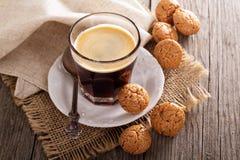 Svart kaffe i ett exponeringsglas med mandelkakor Arkivfoton