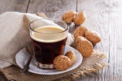 Svart kaffe i ett exponeringsglas med mandelkakor Fotografering för Bildbyråer