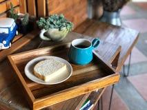 Svart kaffe i grön kopp och hemlagat bröd i den vita maträtten på trämagasinet royaltyfri fotografi