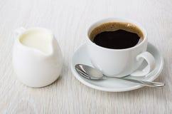 Svart kaffe i koppen, sked på tefatet, tillbringare av mjölkar Arkivfoton