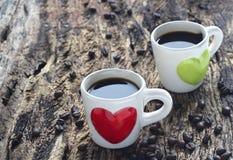 Svart kaffe i röd och grön hjärtakopp på trä Arkivbilder