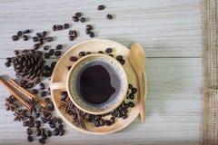 Svart kaffe i träkopp- och kaffebönor spiller på träbakgrund royaltyfri foto