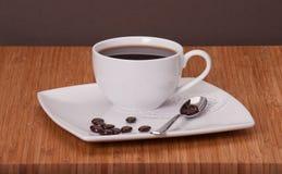 Svart kaffe i vit kuper royaltyfria bilder