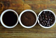 Svart kaffe, jordkaffe och kaffebönor i vita koppar Arkivbild