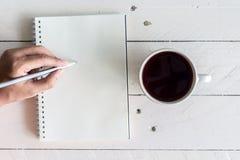 Svart kaffe med anteckningsboken och blyertspennan på träbakgrund royaltyfri bild