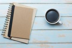 Svart kaffe med anteckningsboken och dagboken på trägolv Arkivbild