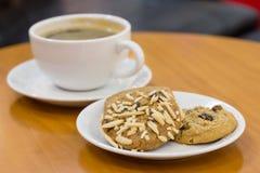 Svart kaffe med kakor på tabellen Arkivbild