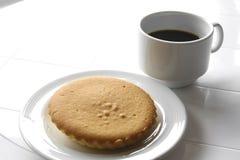 svart kaffe med smörkakan Arkivbild