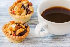 Svart kaffe och frukt som är syrliga på trätabellen Arkivfoton