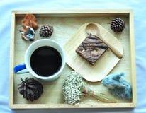 Svart kaffe och nisse på träplattan Arkivbilder