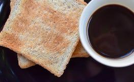 Svart kaffe och rostat bröd för helt vete på den svarta plattan, lätt mål för frukost i morgonferien Royaltyfri Fotografi