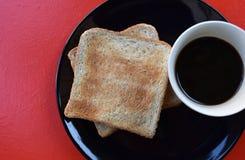 Svart kaffe och rostat bröd för helt vete på den svarta plattan på den röda tabellen, lätt mål för frukost i morgonferien Royaltyfri Bild