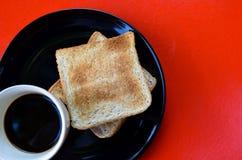 Svart kaffe och rostat bröd för helt vete på den svarta plattan på den röda tabellen, lätt mål för frukost i morgonferien Royaltyfria Foton