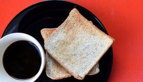 Svart kaffe och rostat bröd för helt vete på den svarta plattan på den röda tabellen, lätt mål för frukost i morgonferien Royaltyfri Fotografi
