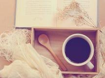 Svart kaffe och sked på trämagasinet med boken, retro filter Arkivfoto