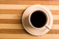 Svart kaffe på träbräde Arkivbild