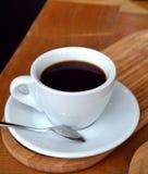 Svart kaffe per den glass koppen på en trätabell Royaltyfria Foton