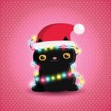 Svart katt för jul med girlanden och den santa hatten Royaltyfri Bild