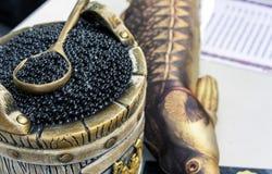 Svart kaviar i en trumma med en sked royaltyfria bilder