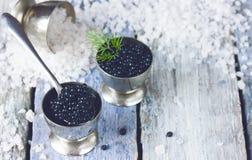 Svart kaviar i metalltenn i is på den gamla blåa träbakgrunden Royaltyfria Bilder