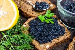 Svart kaviar på en smörgås Sätt en silversked på smörgåsen royaltyfri foto