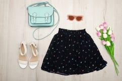 Svart kjol, exponeringsglas, vita skor, handväska och en bukett av tulpan trendigt begrepp spelrum med lampa Arkivbild