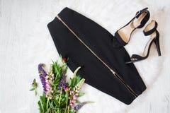 Svart kjol och skor buketten blommar wild Vit bakgrund Fotografering för Bildbyråer