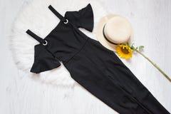 Svart klänning på den vita päls, hatten och solrosor Trendig concep Fotografering för Bildbyråer