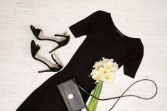 Svart klänning, skor, koppling och en bukett av påskliljor trendigt begrepp spelrum med lampa Royaltyfri Fotografi