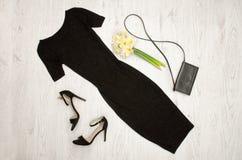 Svart klänning, skor, koppling och en bukett av påskliljor trendigt begrepp spelrum med lampa Arkivbilder