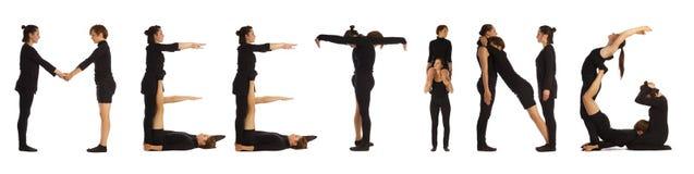 Svart klätt folk som bildar ordet MÖTE Fotografering för Bildbyråer
