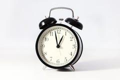 Svart klassisk klocka på vit bakgrund Royaltyfria Foton