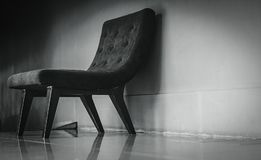 Svart klassisk stol med unik design i tom toalett nära betongväggen på mörk och dramatisk bakgrund En tom fåtölj arkivfoto