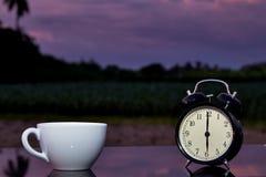Svart klockaklocka och varmt kaffe för kopp på den wood tabellen i trädgården Royaltyfri Foto