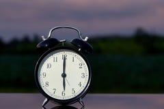 Svart klockaklocka på den wood tabellen i trädgården Royaltyfria Bilder