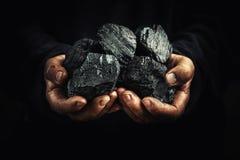 Svart kol i händerna, tung bransch, uppvärmning royaltyfri bild