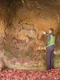 Svart kolmålarfärg av mänsklig jakt på sandstenväggen, kopia av den förhistoriska bilden Abstrakt barnkonst i grotta Man på målni Arkivbilder