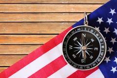 Svart kompass och amerikanska flaggan på träbräde arkivbild