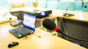 Svart konferensmikrofon och dator som används för möten och t Arkivfoto