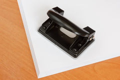Svart kontorshålstansmaskin på en paper bunt Arkivfoton